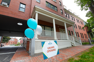 balloons and grand opening sign in front of an affordable housing development