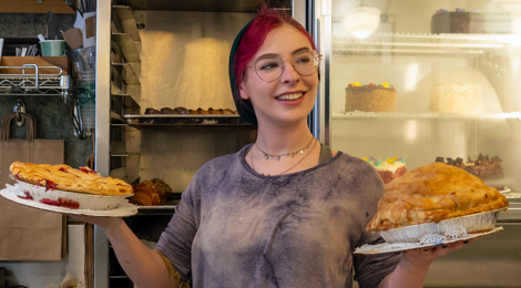 woman smiling as she holds two pies